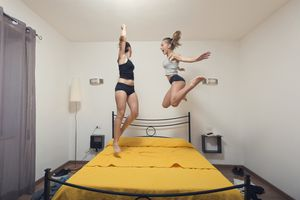 Two young women jumping and dancing on bed