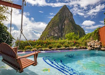 A wooden rope swing hanging over a pool overlooking a mountain in St Lucia