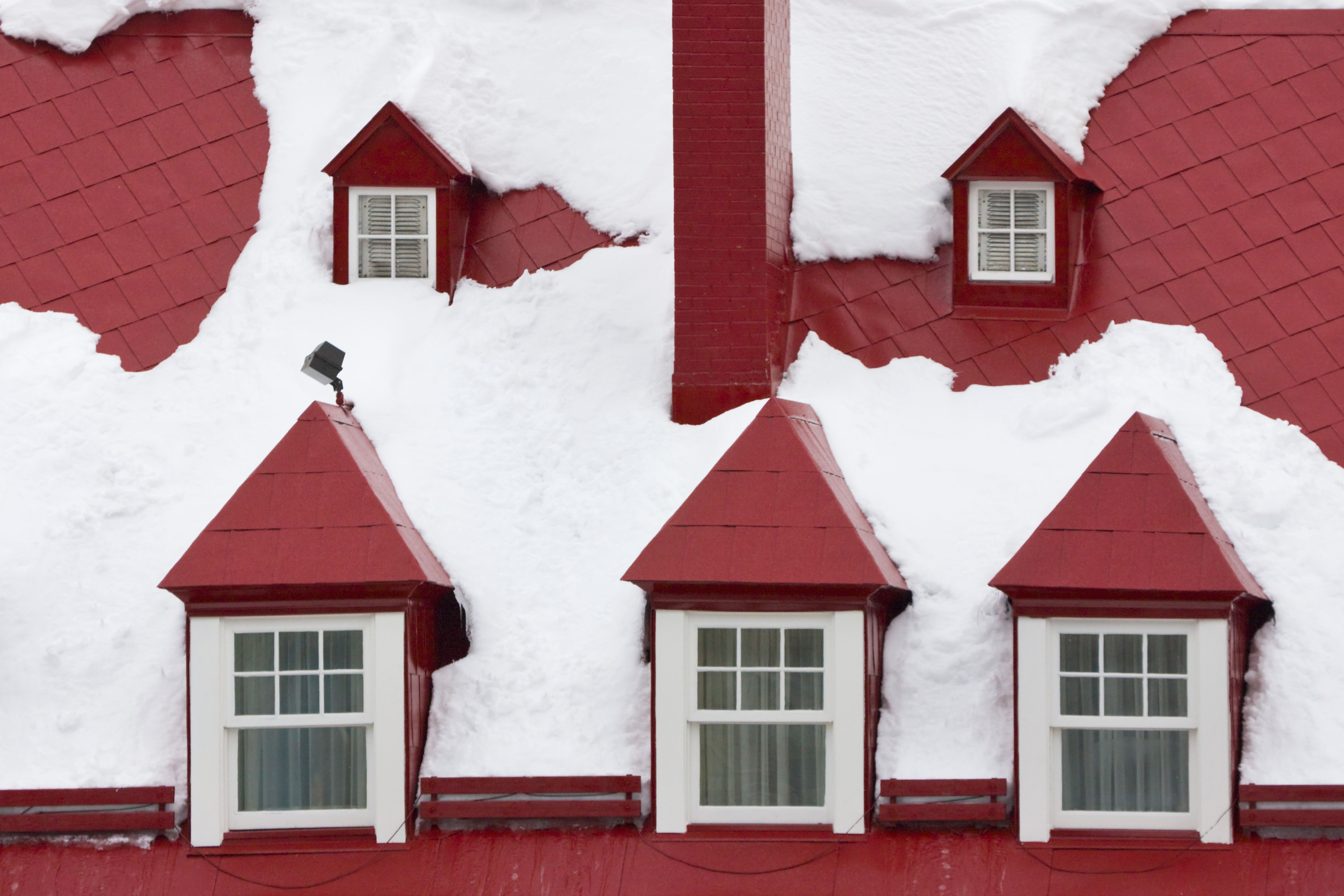 Old houses, red roof and window covered with snow, Quebec City, Canada