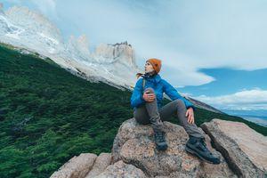 Girl wearing jacket sitting on top of rock