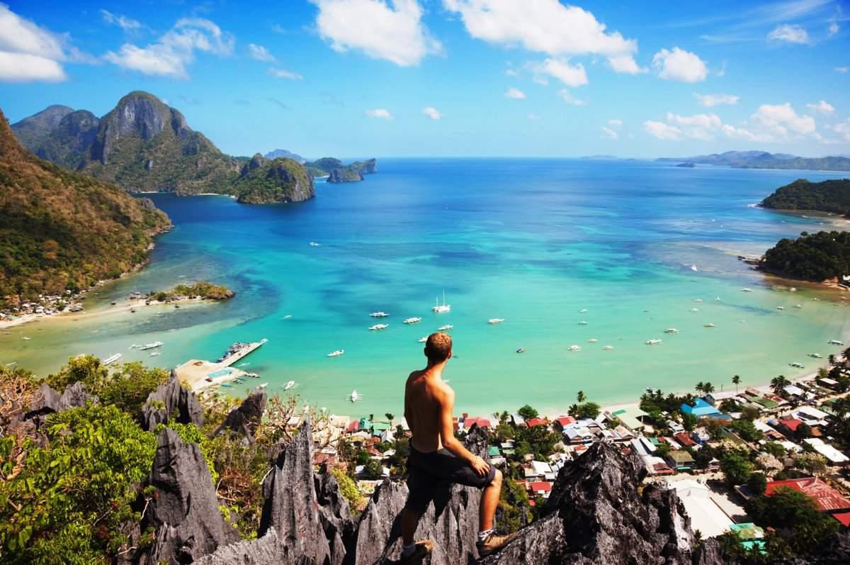 Hiker viewing El Nido Bay and town, Palawan, Philippines.