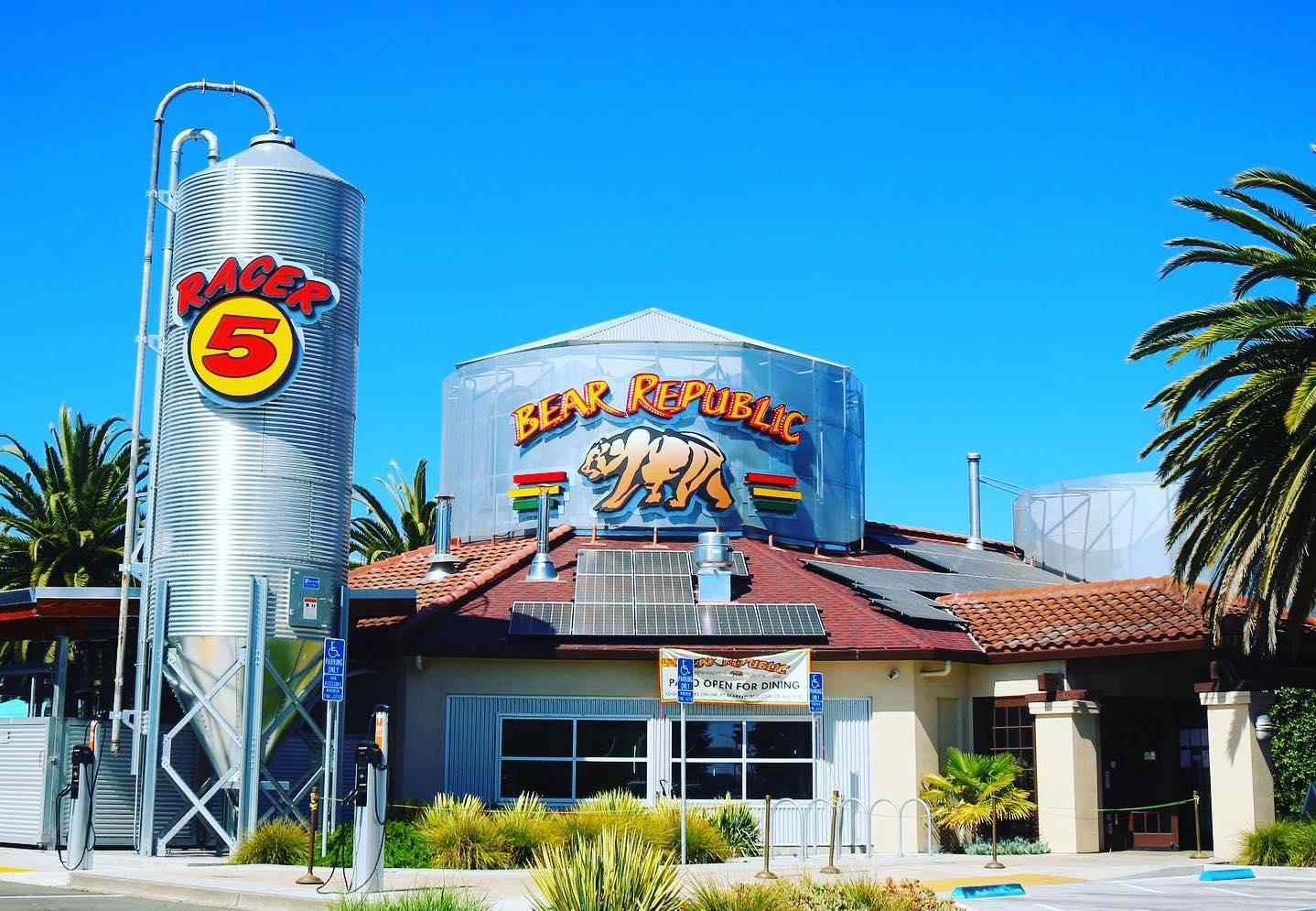 exterior of a one floor brewery. There is a tall metal silo with a sign that reads