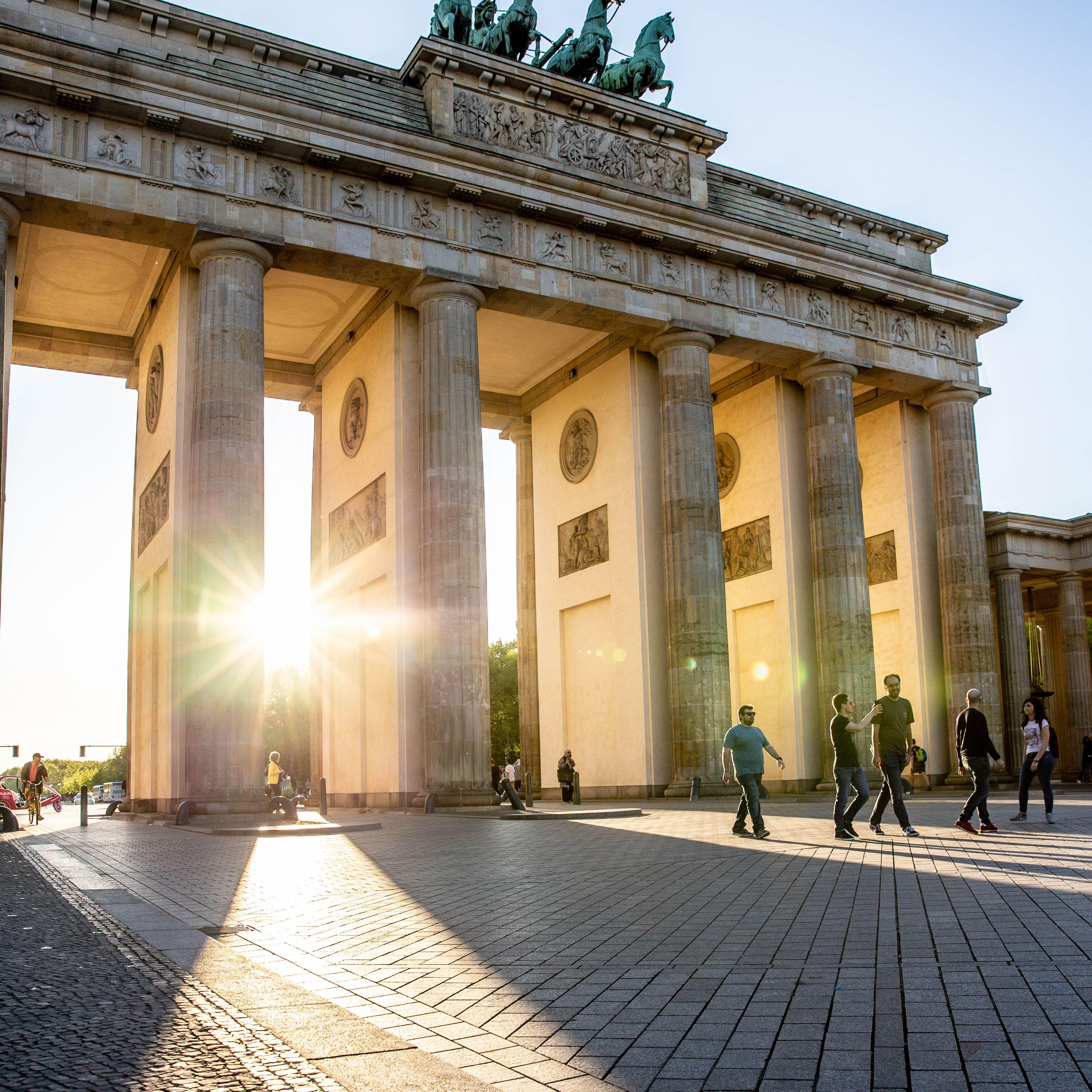 El sol brillando a través de las piernas de la Puerta de Brandenburgo