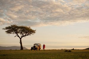 Maasai warrior stands beside a vintage safari vehicle in Kenya