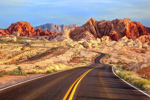 Empty paved road in Valley of Fire state park with dramatic rock cliffs in the distance