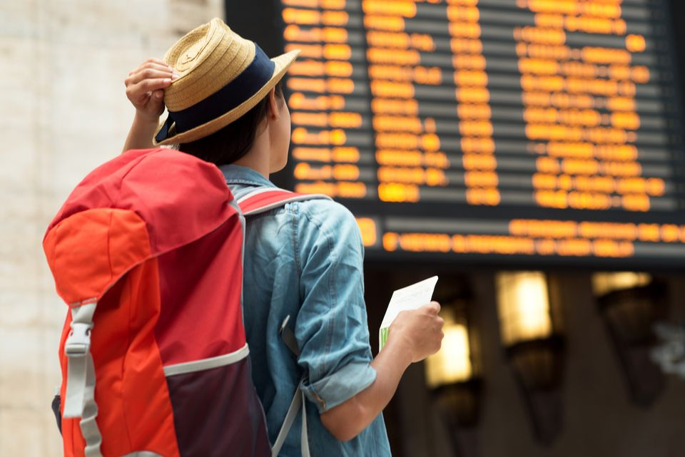 Woman looking at a train departures board