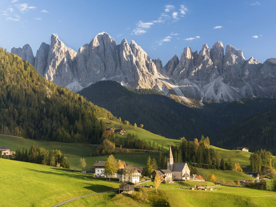 Sharply edged mountains rise above a small Italian village