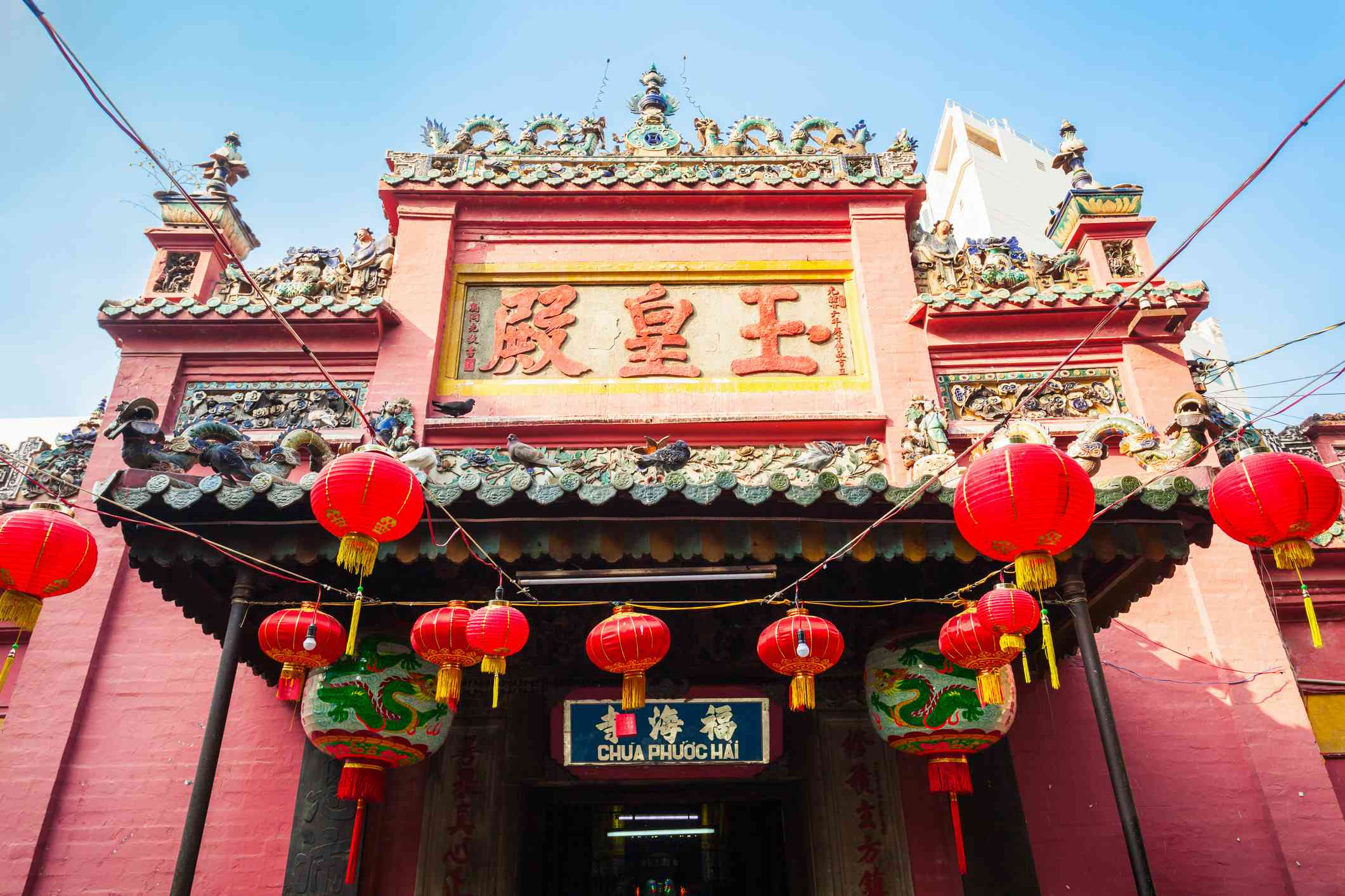 red taoist temple with red lanterns in front
