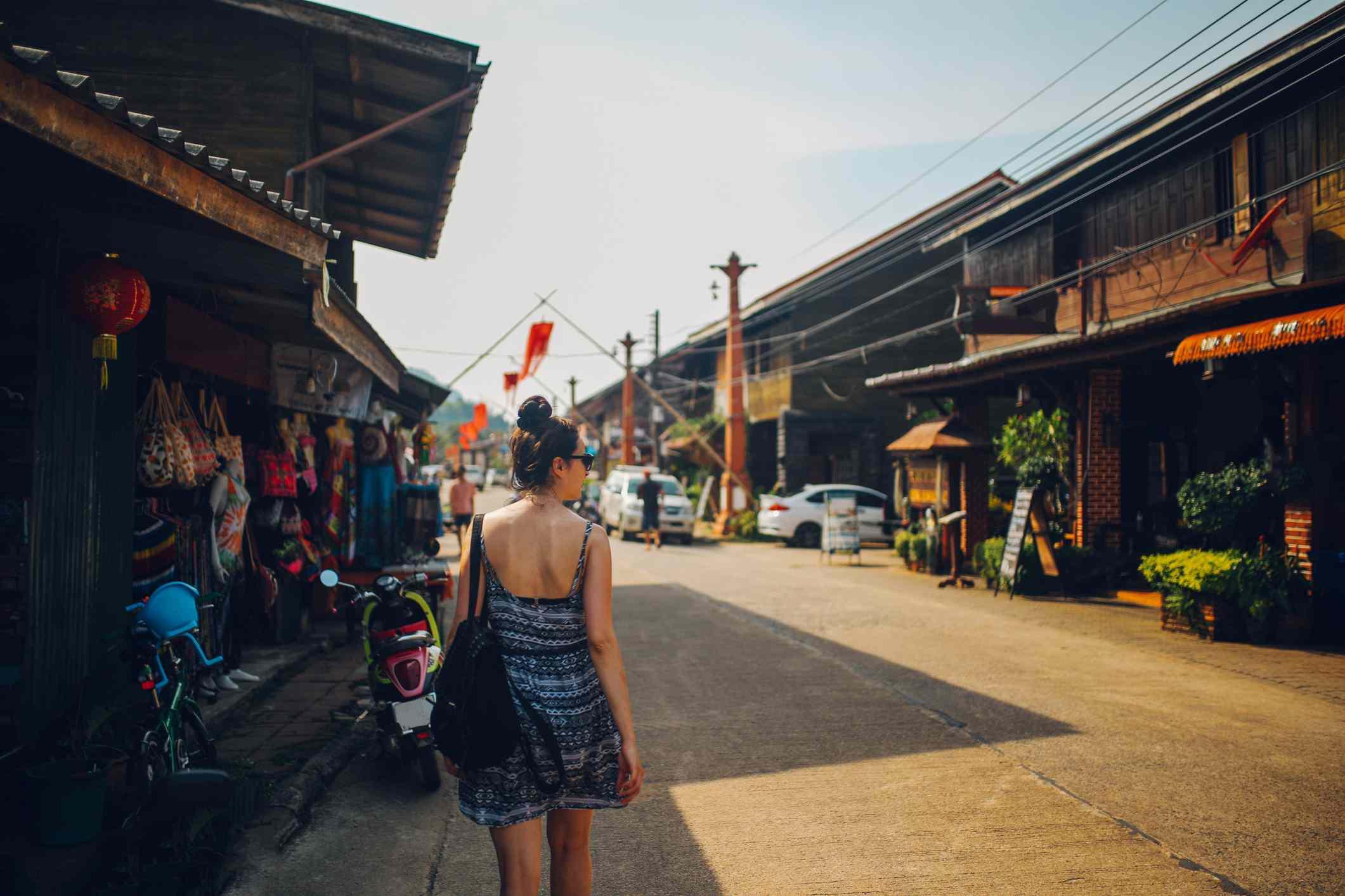 Rear view of young woman walking through Koh Lanta Old Town streets