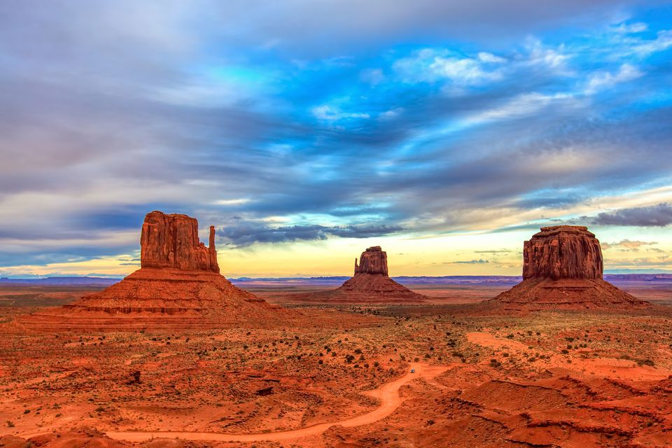 Three large rock formations in Monument Valley just before sunset