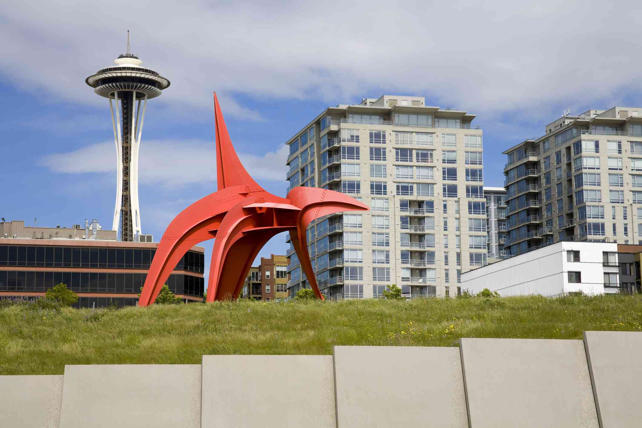 red, abstract sculpture on grass with the Seattle space needle in the background