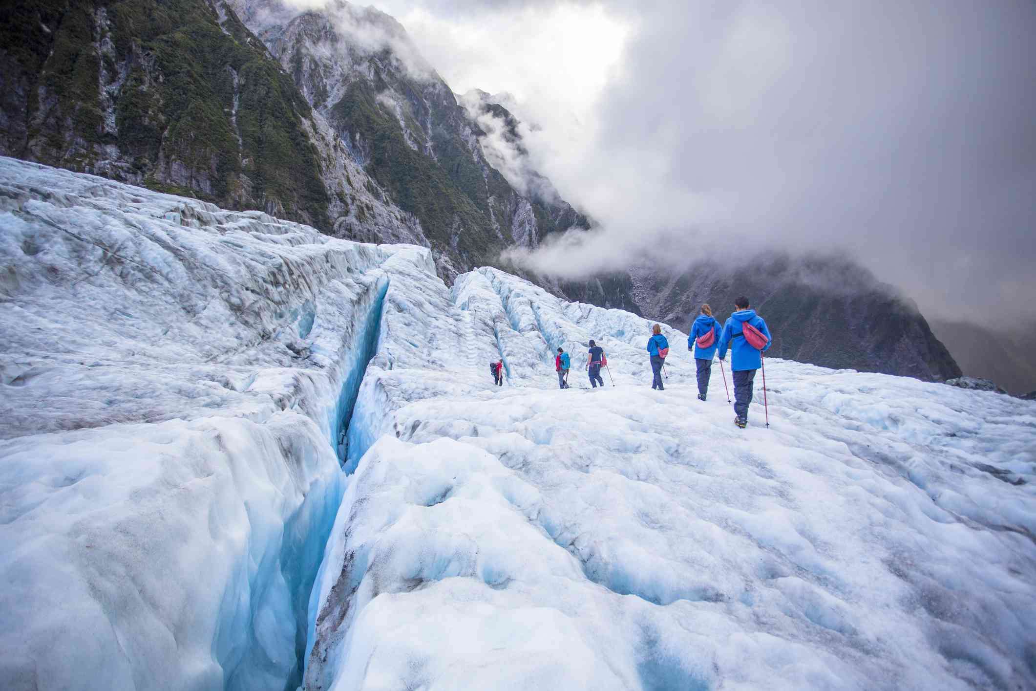 people walking on a glacier with clouds and mountains behind