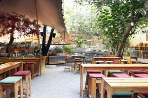 Wooden tables and stools on the garden patio at six d.o.g.s. in Athens
