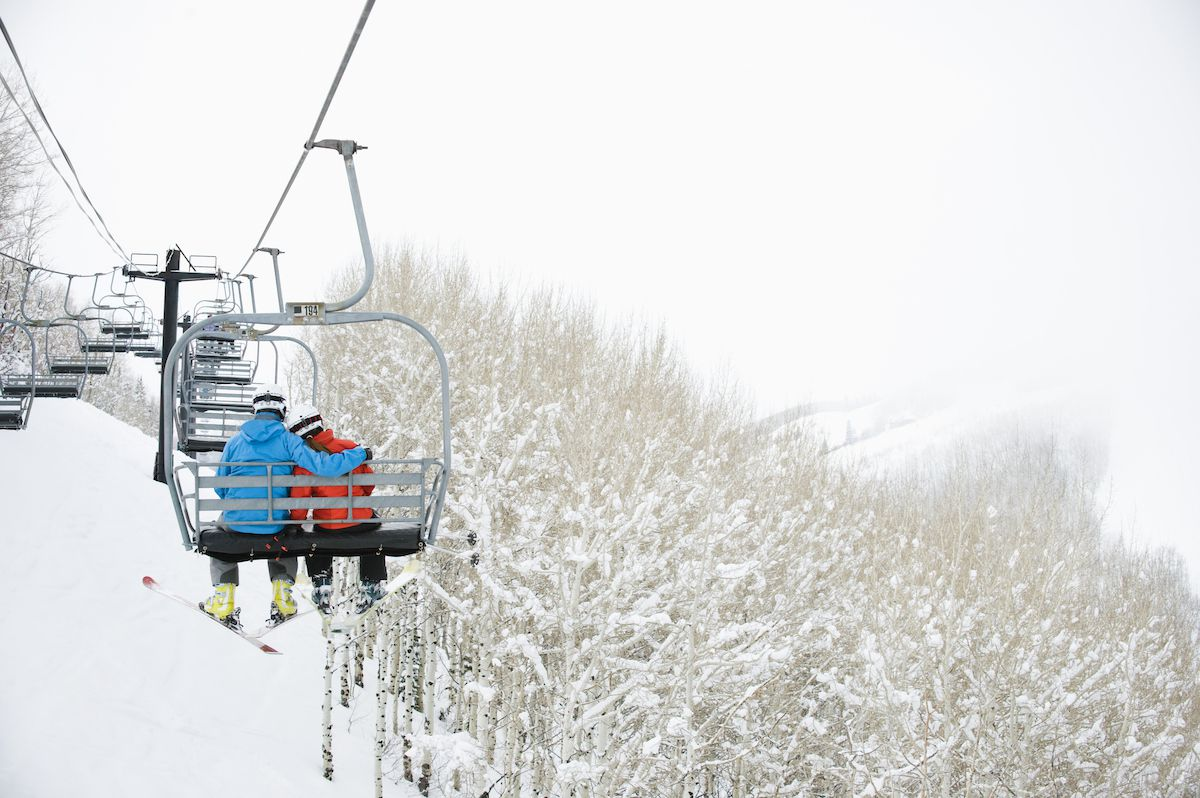 Skiers ride a lift to the top of a snowy mountain