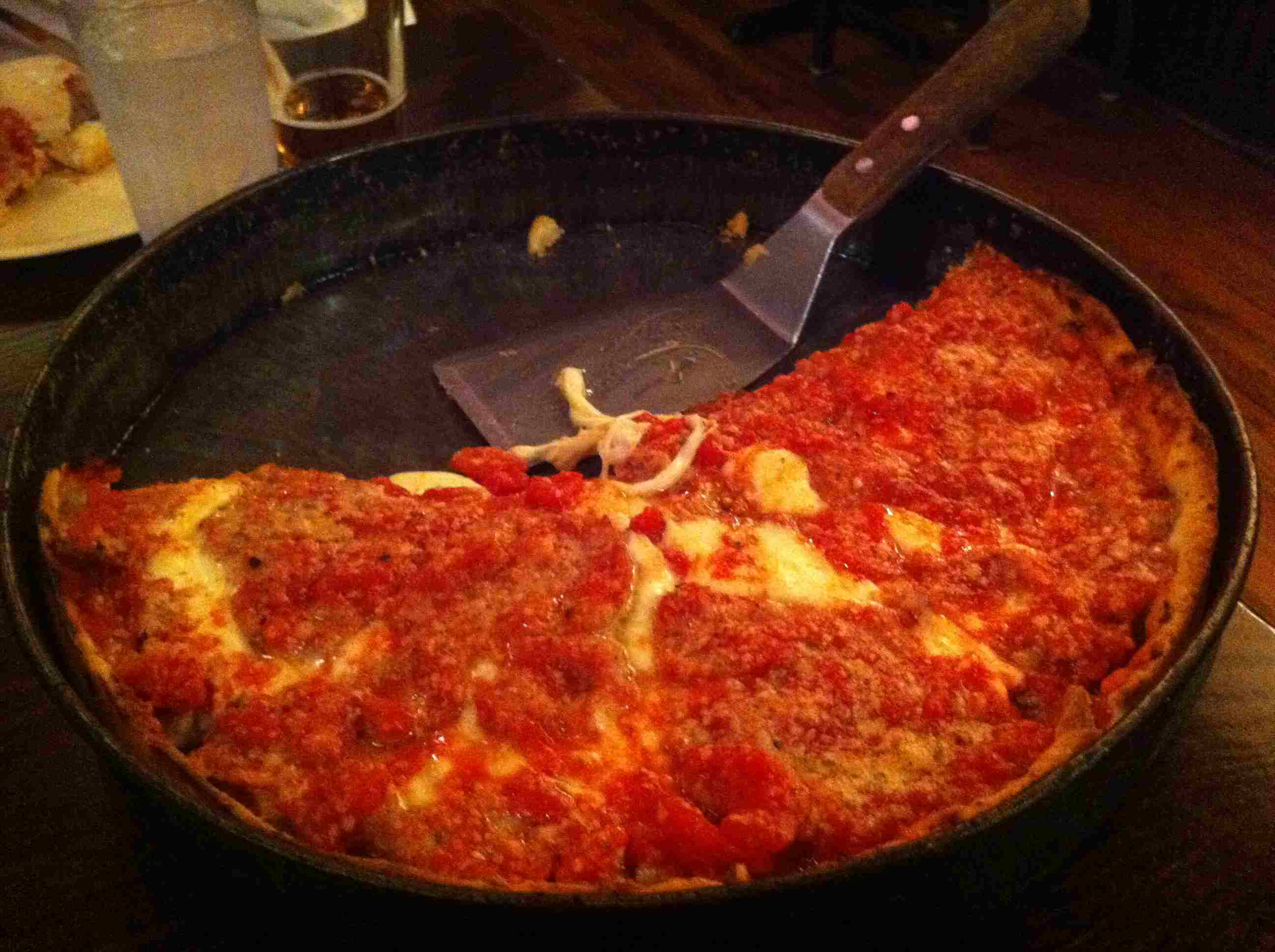 Половина глубокого блюда чикагского стиля пиццы от пиццерии Лу Malnati в