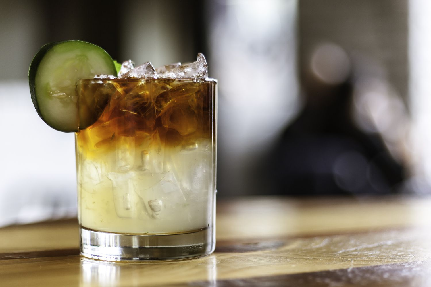 Glass with ice, lime juice at the bottom and a mix of Espolon Blanco tequila and Aperol with a cucumber garnish