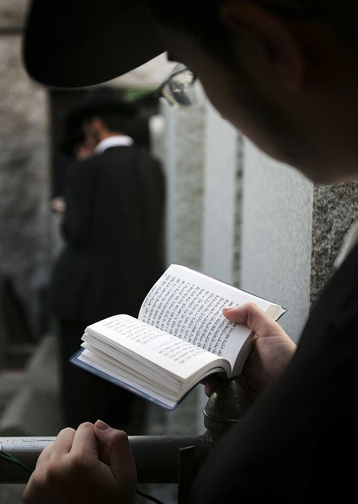 Jewish man holding a religious text