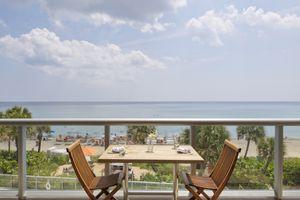 Empty table on restaurant balcony overlooking beach