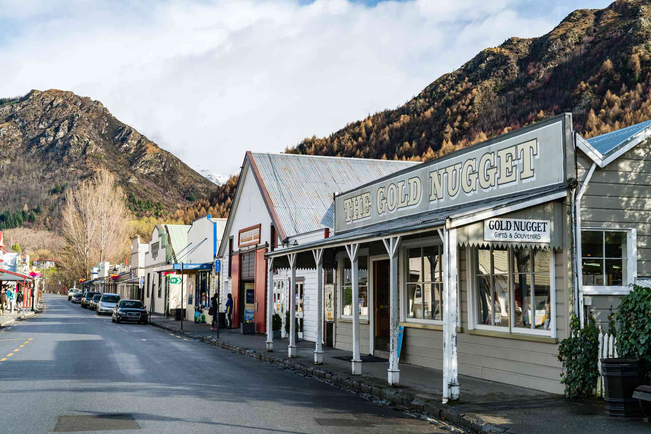 row of shops on a street through a town with mountains in background