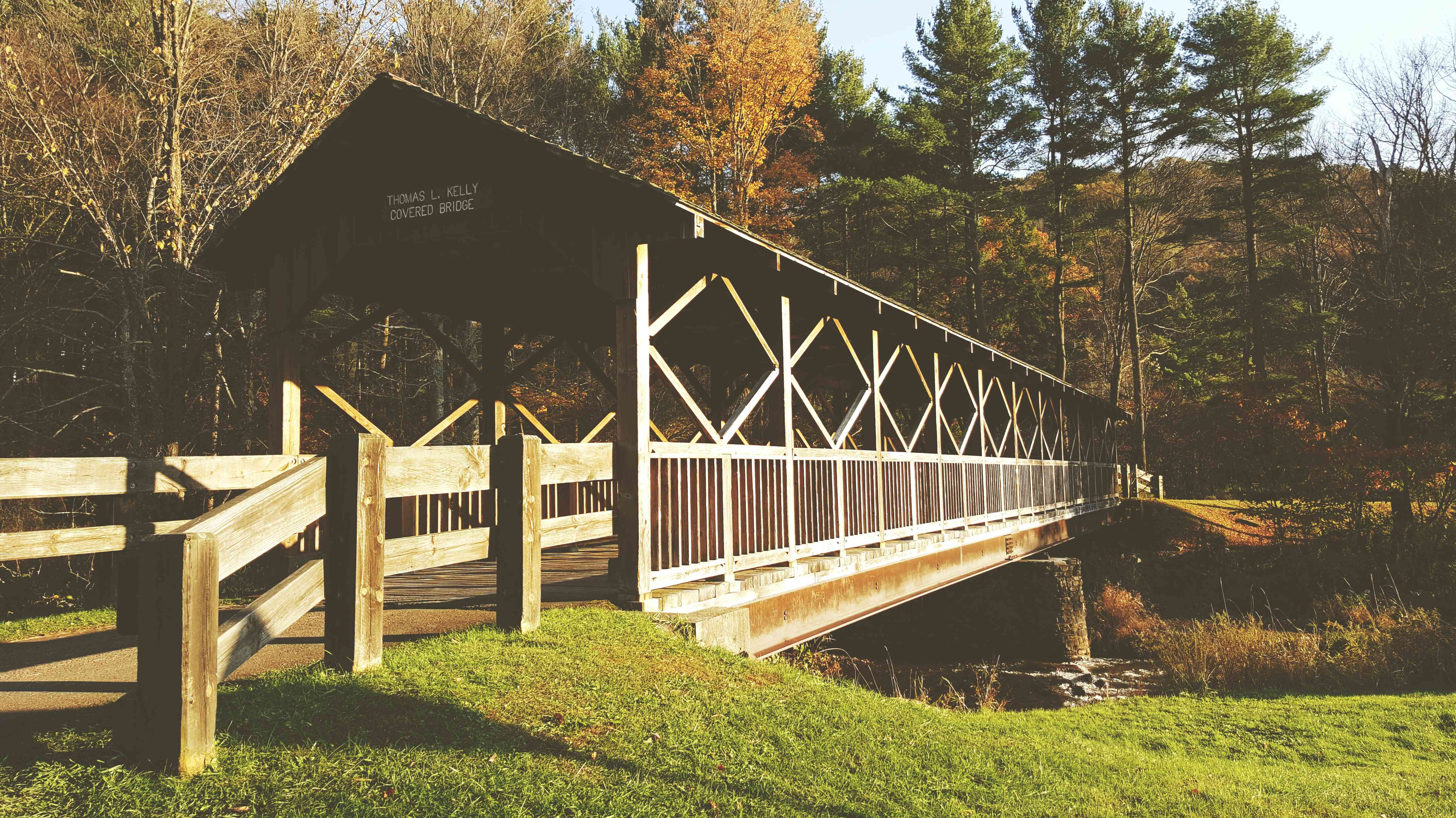 wooden bridge with roof over a river surrounded by autumnal trees