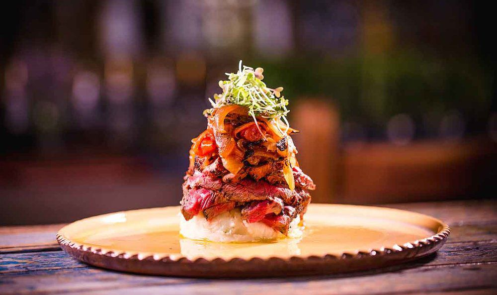 round plate with an artfully plated tower of meat, vegetables, and sprouts