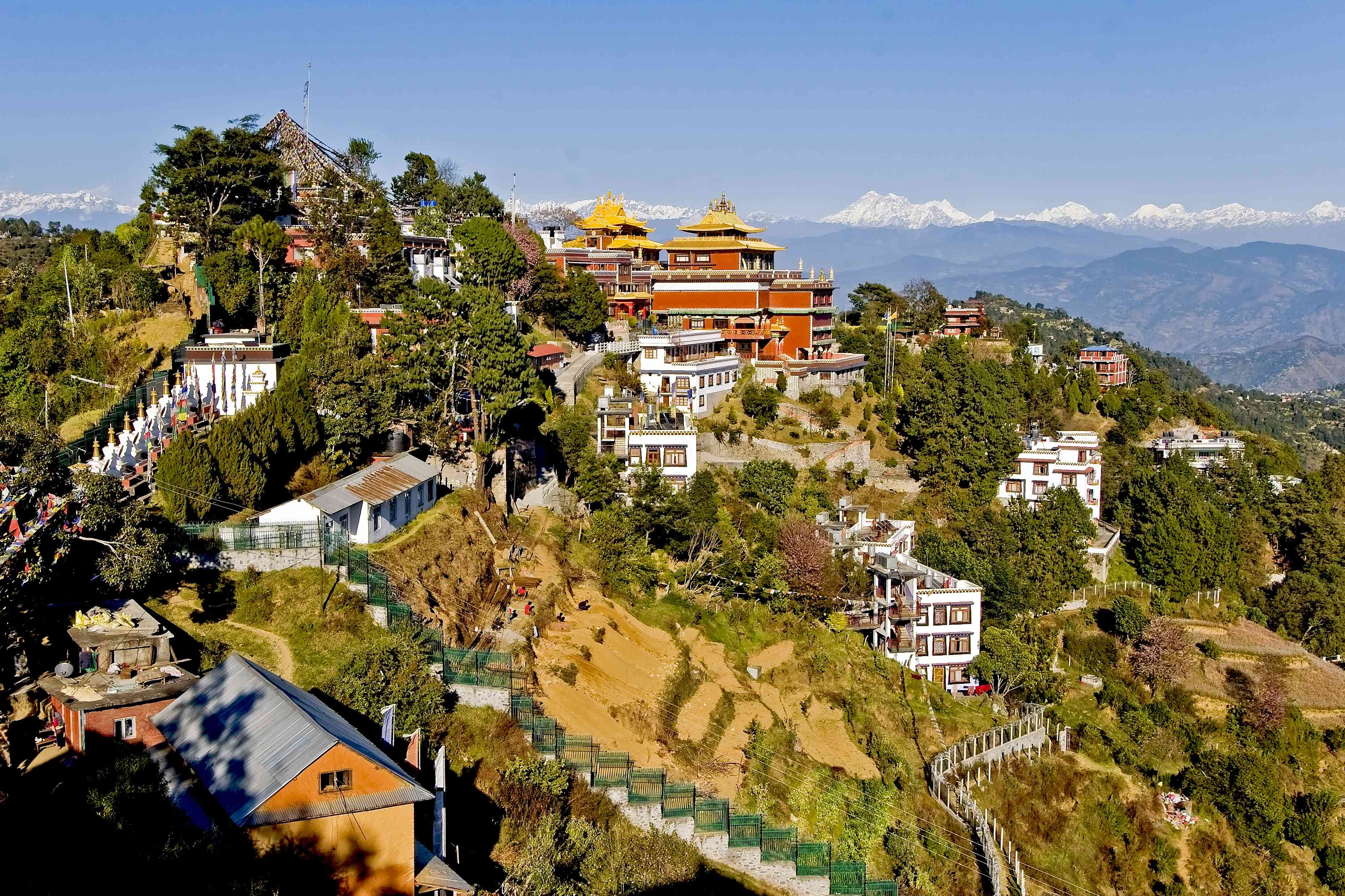 Buddhist monastery and houses on a hillside with snow peaks in distance