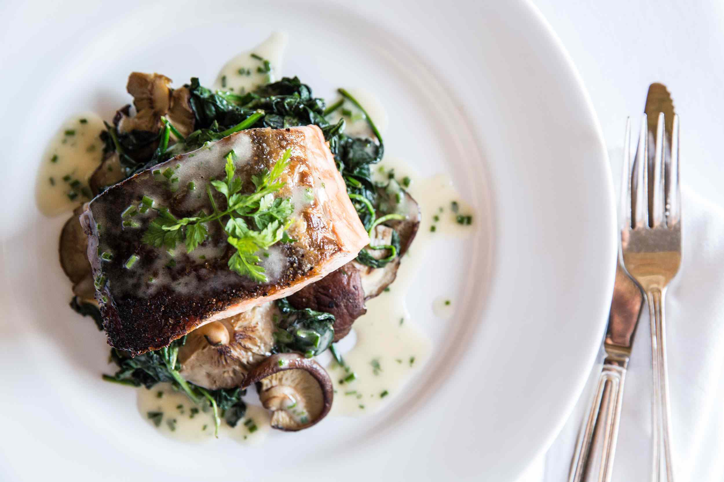 overhead shot of seared fish on top of mushrooms and spinach, garnished with cilantro. There is a fork and knife to the right of the plate