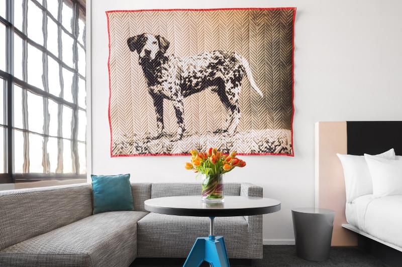 A bedroom at Museum Hotel Oklahoma City that features a painting of a dog and a couch seating area.