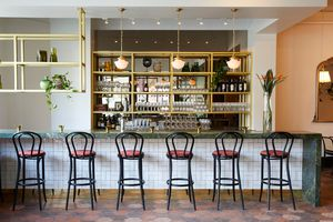 high chairs at a marble and tile bar gold light fixtures and shelving
