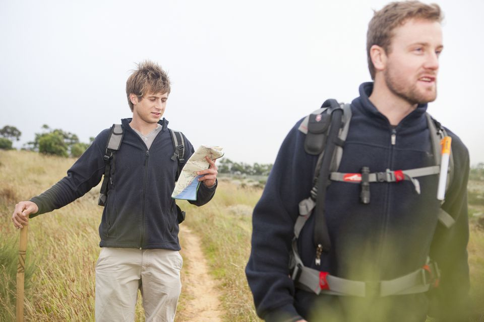 Two male hikers with backpacks and map