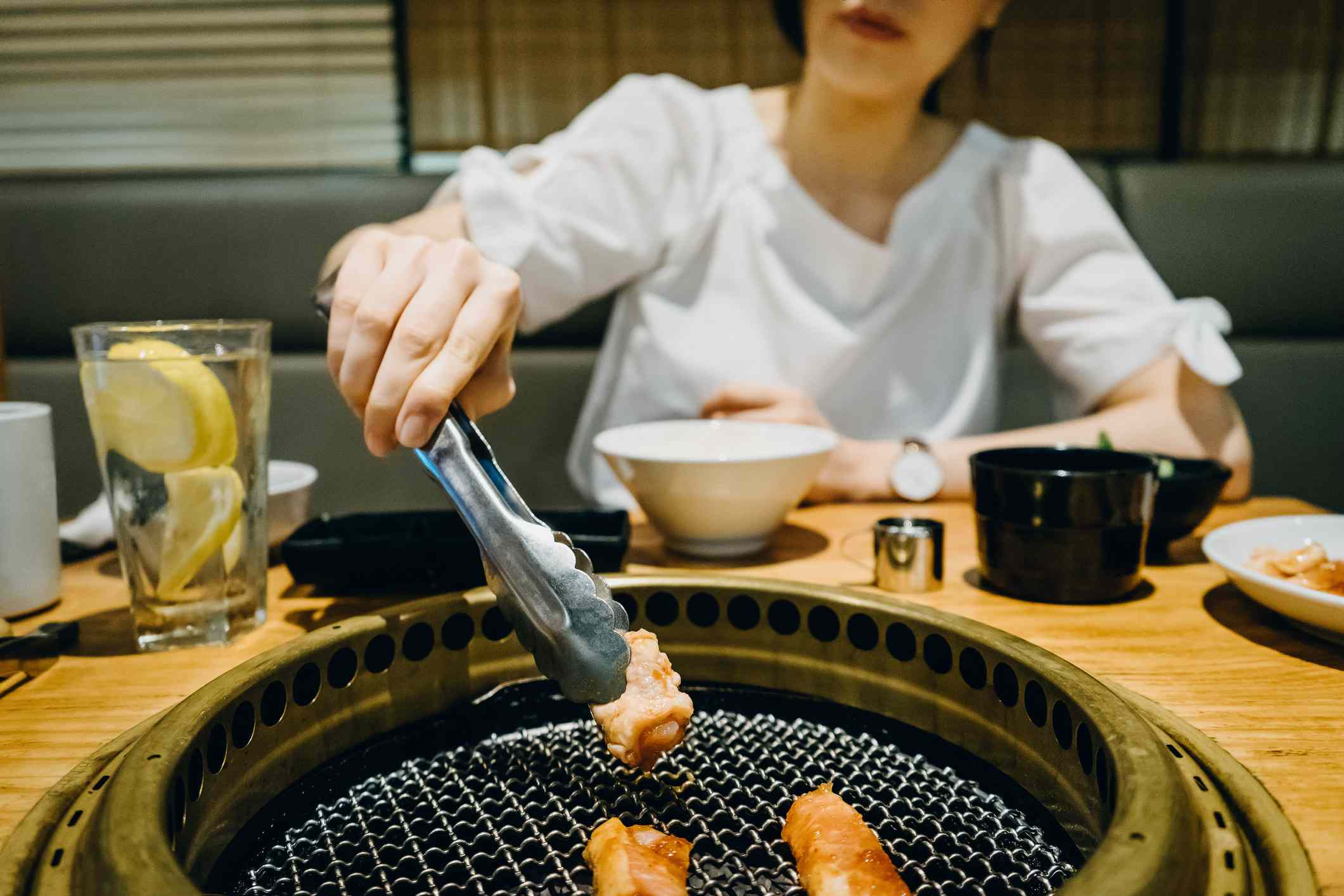 Japanese woman moving grilled intestines with tings on a in-table charcoal gril