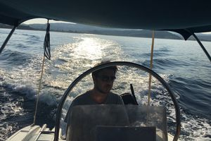 Portrait Of Young Man Driving Motorboat In Sea