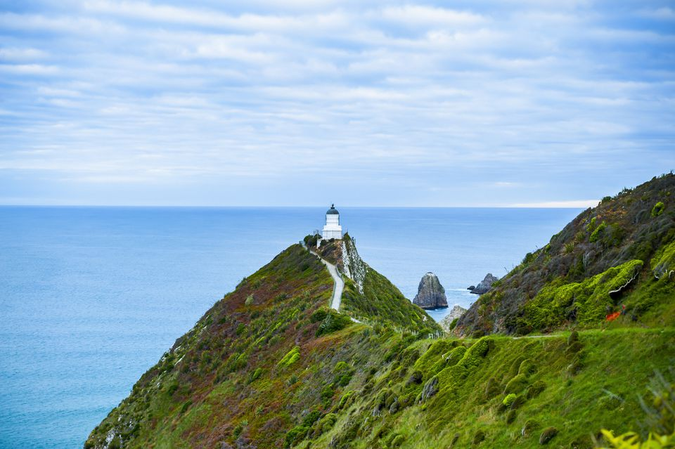 lighthouse at the end of a green headland with blue sea and sky behind