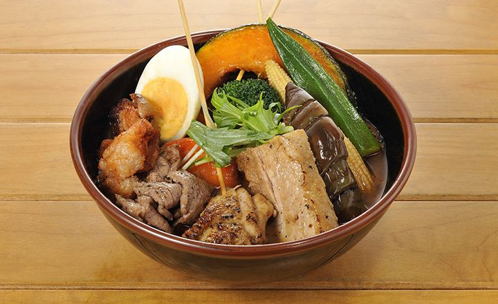 bowl of japanese curry filled with skewered mean, vegetables and half a boiled egg.