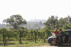 Couple standing by a car looking at map, with San Gimignano in the distance