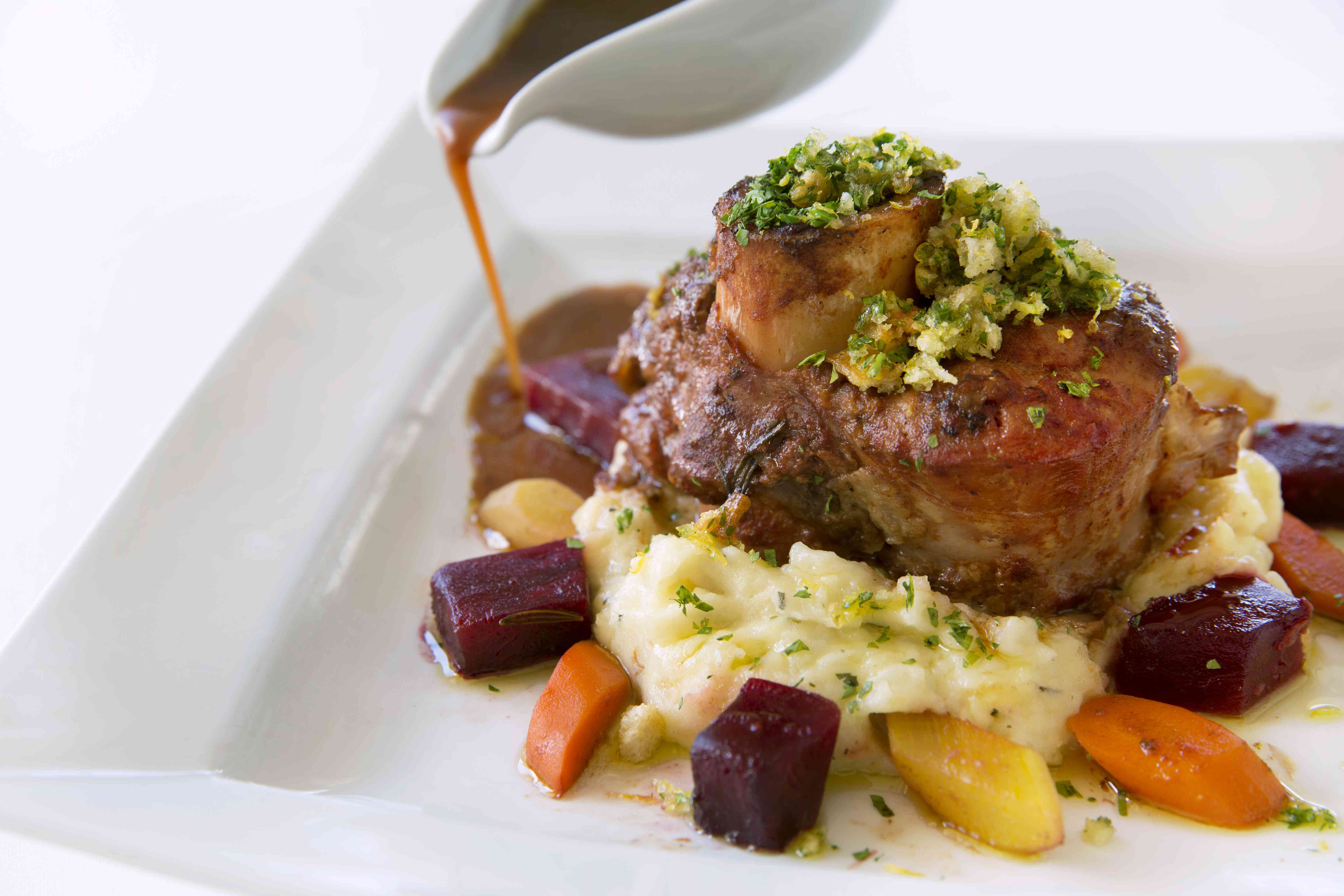 Veal ossobuco on a bed of mashed potatoes, with beets and carrots.