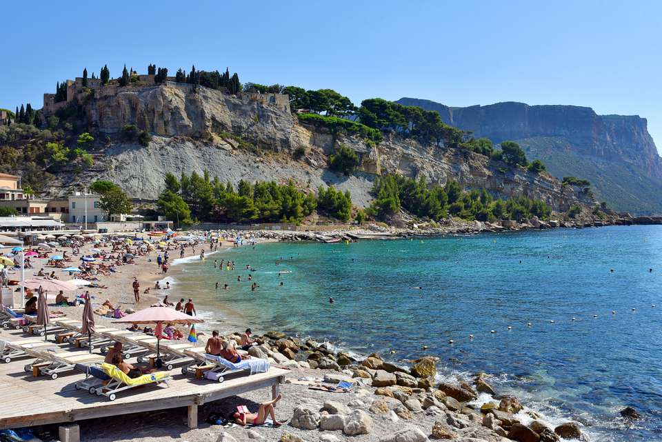 A crowded beach in Cassis, France with rock fromations in the distance