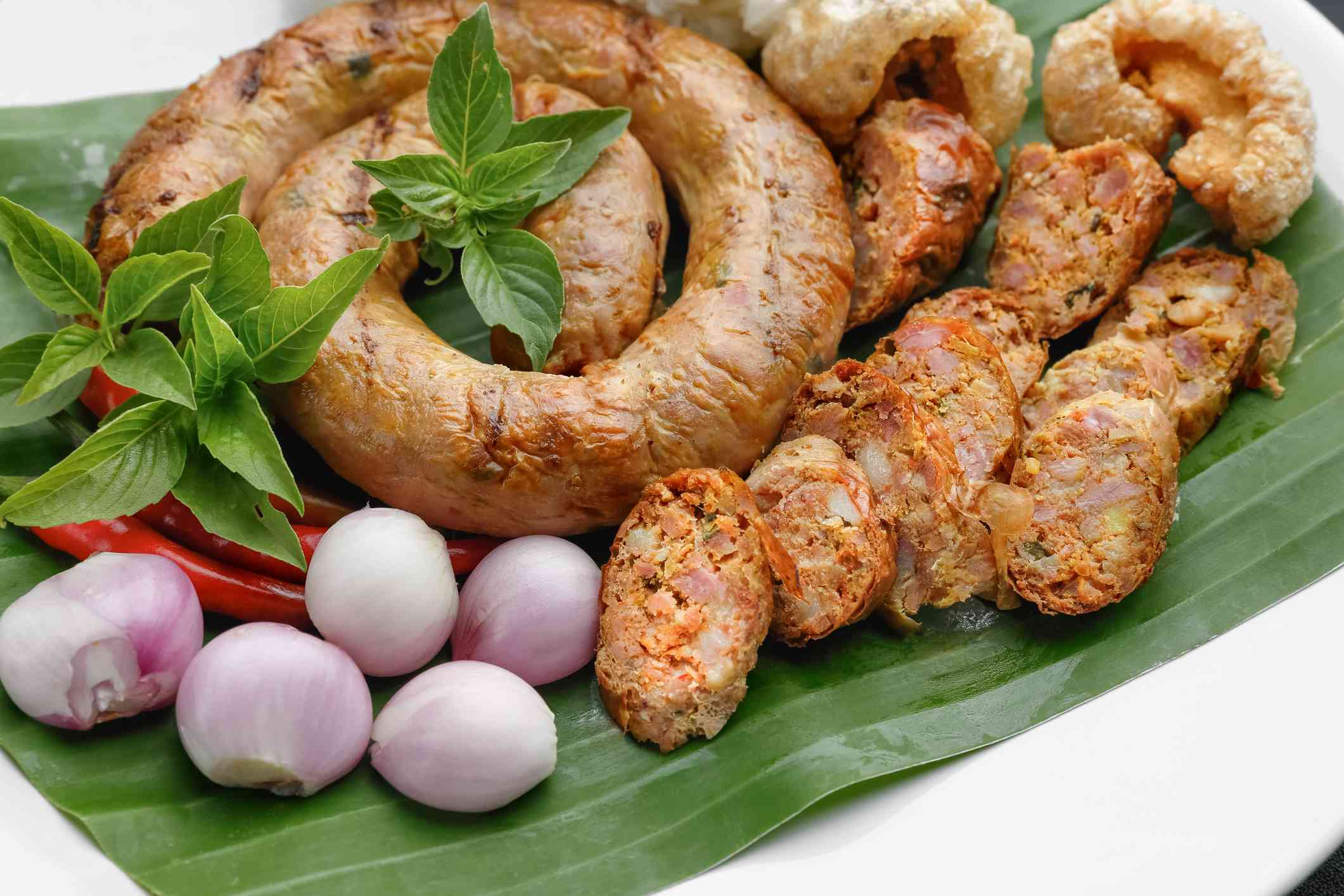 sausage link and slices of sausage on a banana leaf with small onions, chillies, and a green herb