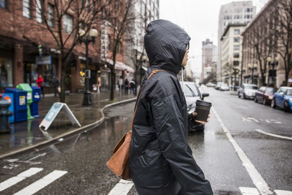 Young woman on rainy pedestrian crossing, Seattle, Washington State, USA