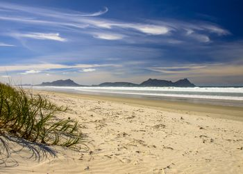 wispy clouds in deep blue sky with rocky headlands in the sea and white sand beach