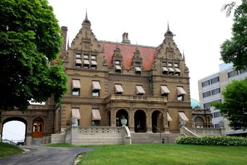 Exterior view of Pabst Mansion in Milwaukee, WI. Large and stately brick mansion with red roof and several spires set back on a green lawn surrounded by trees.