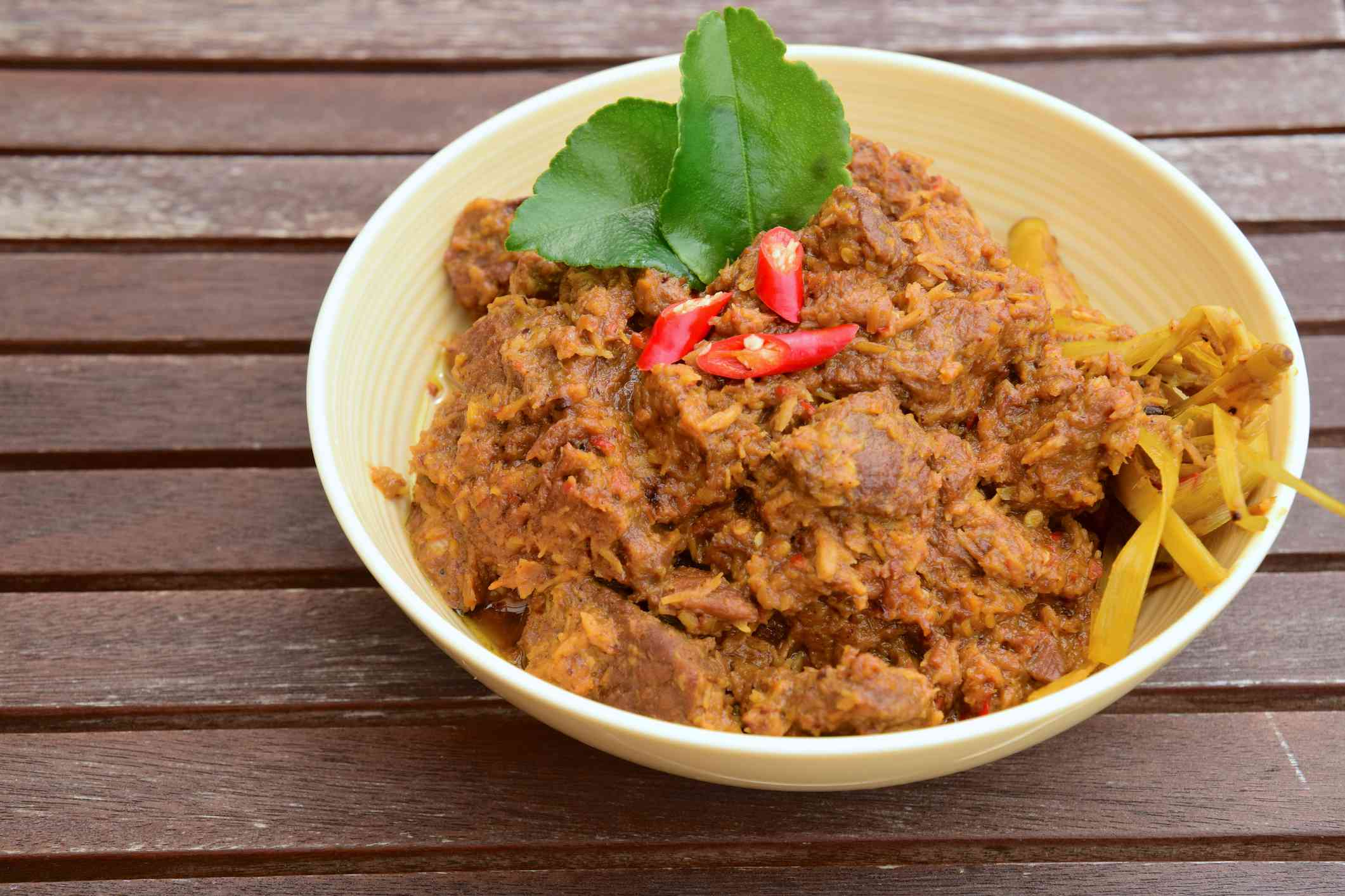 The popular Indonesian spicy beef stew in a bowl with bamboo shoots and garnishes