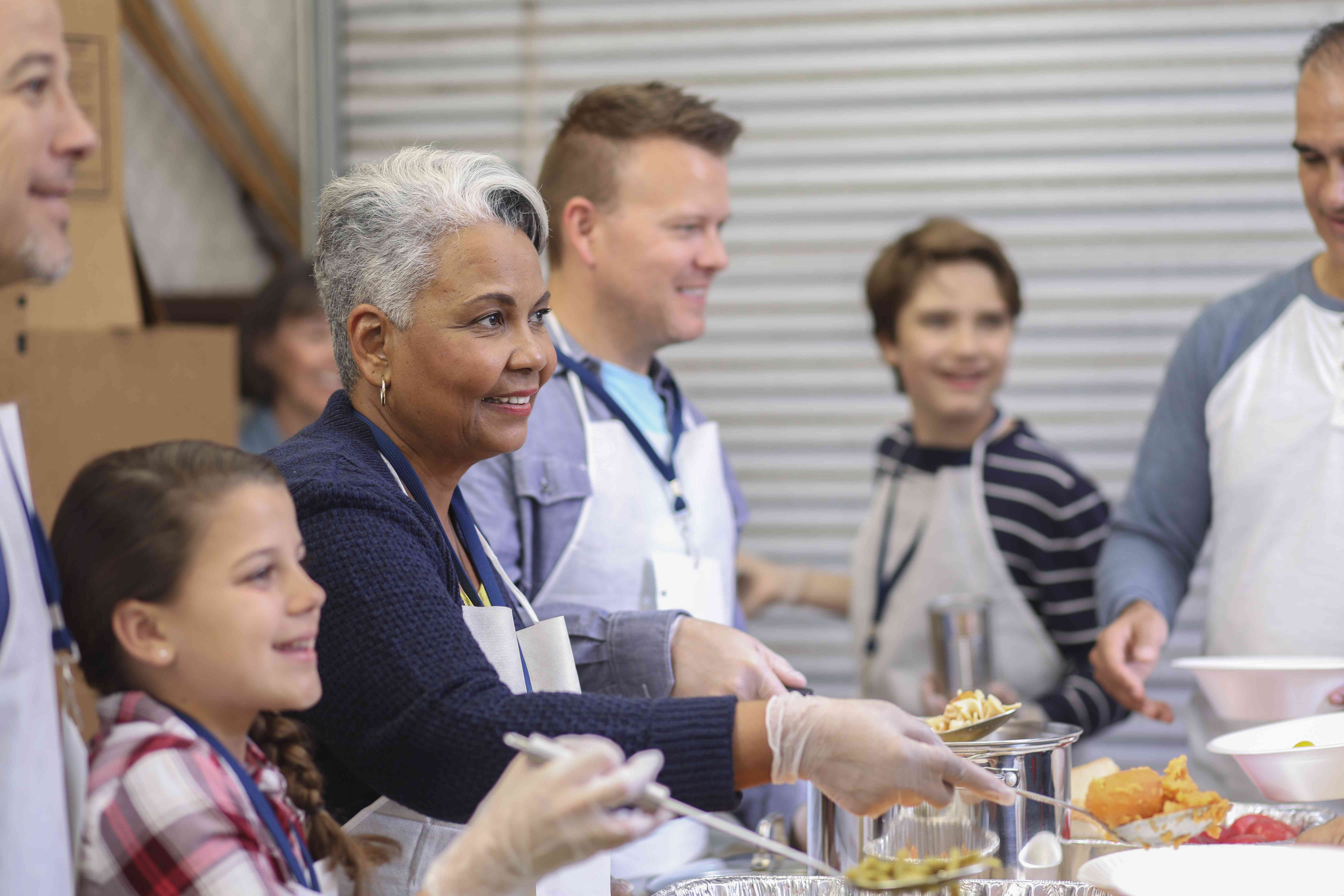 Multi-ethnic group of volunteers serves food at soup kitchen.