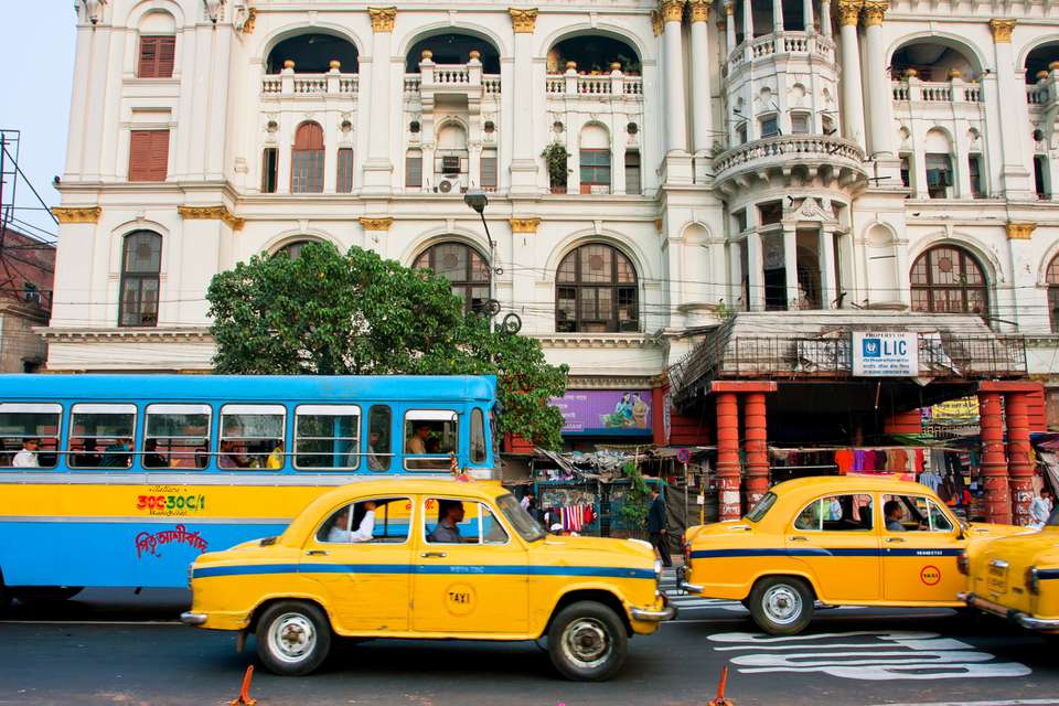 Taxis and a blue bus on a street in kolkata