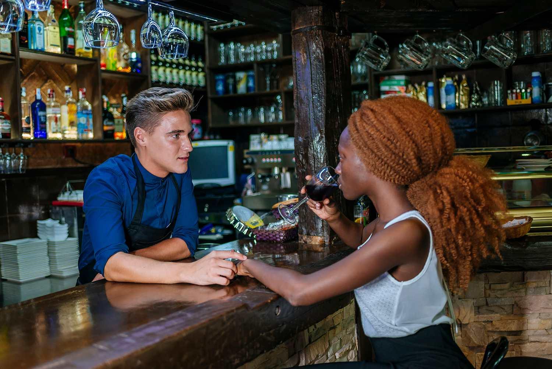 Waiter flirting with woman at a bar
