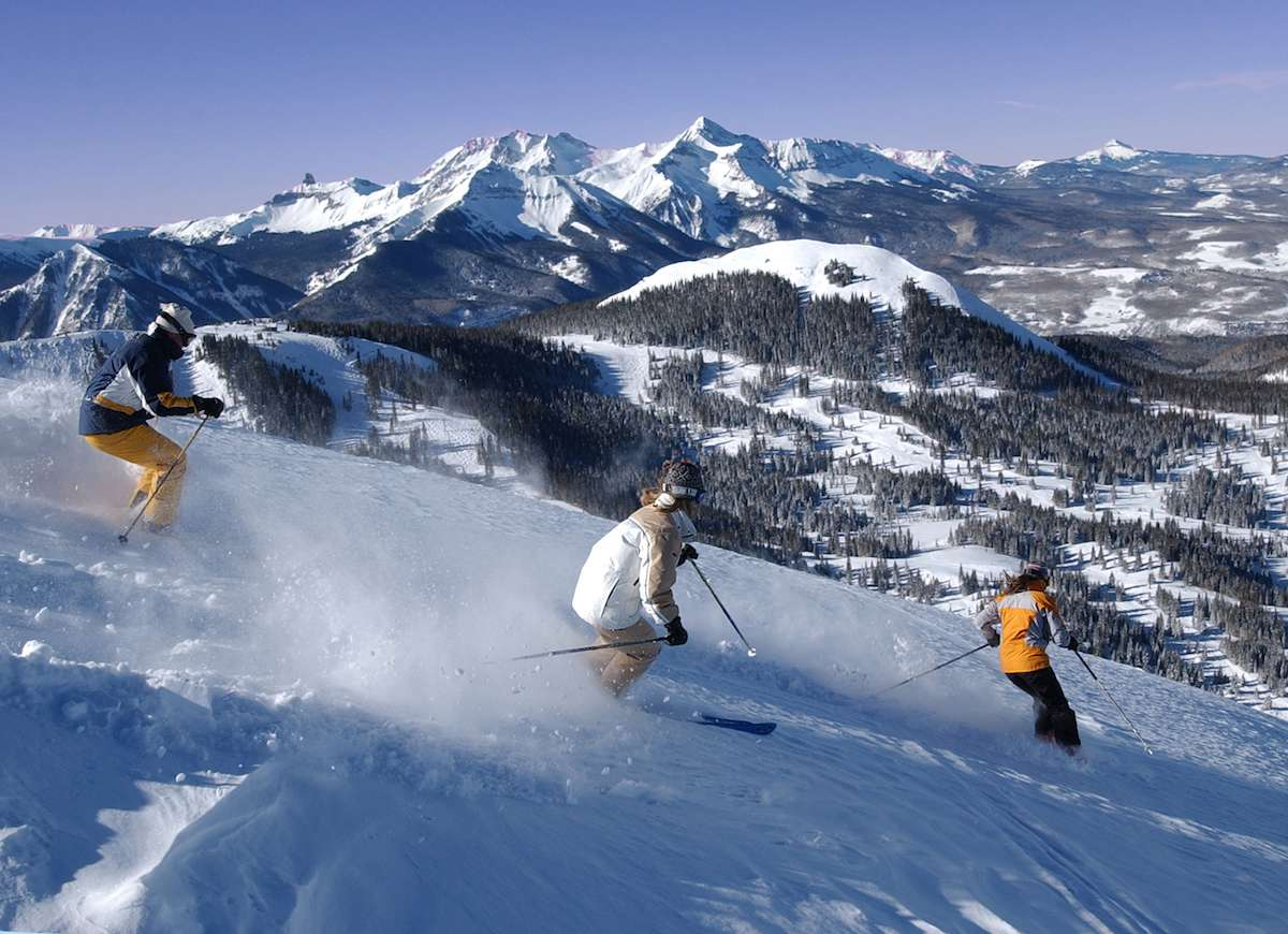 A group of skiers slide through fresh powder with a gorgeous mountain backdrop