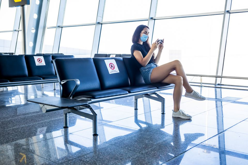 Woman in an airport lounge in a medical mask. Traveling during the coronavirus pandemic