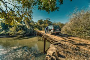 Tourist with car breakdown on a large, rickety wooden bridge in the middle of the wilderness of Paraguay.