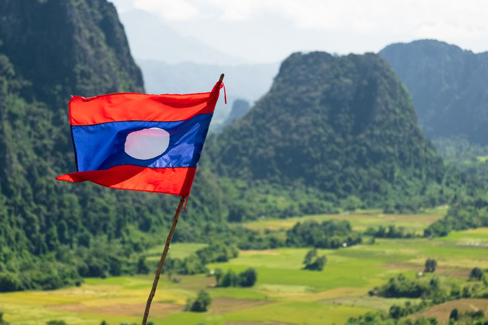 Laos national flag waving in karst formation mountain