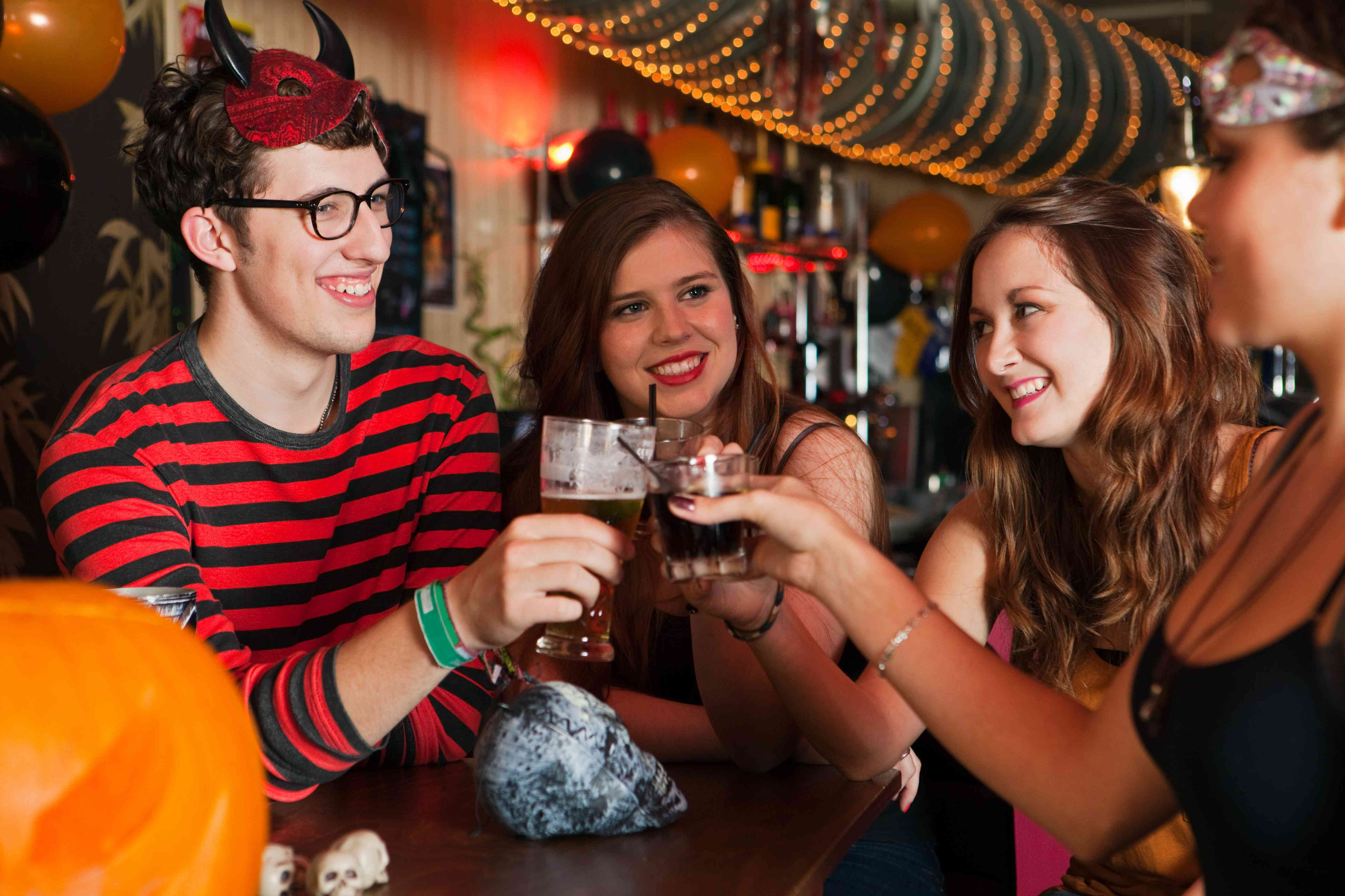 Young friends toasting drinks in bar